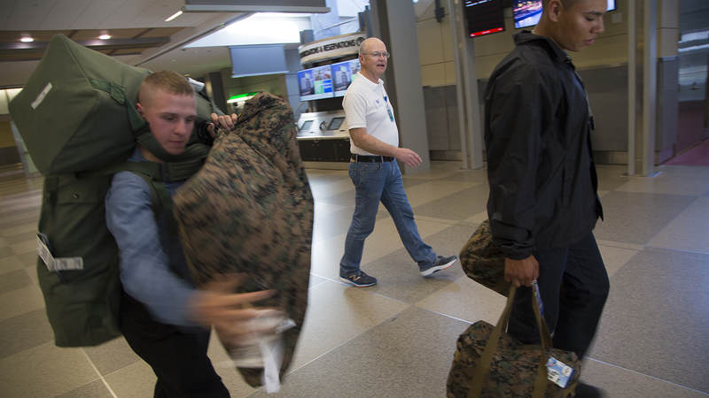 Young Marines balance their bags as USO of North Carolina volunteer JC Cunningham walks them toward a staging area inside Raleigh-Durham International Airport on March 9.