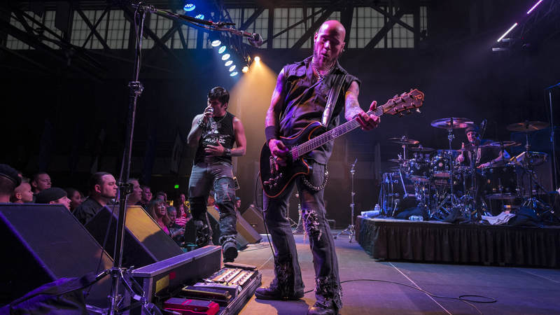 Multi-platinum hard rock band Drowning Pool members C.J. Pierce (center), Jasen Moreno (left) and Mike Luce (right) perform for troops at F.E. Warren AFB in Wyoming on Sept. 11, 2013, as part of their fourth USO tour