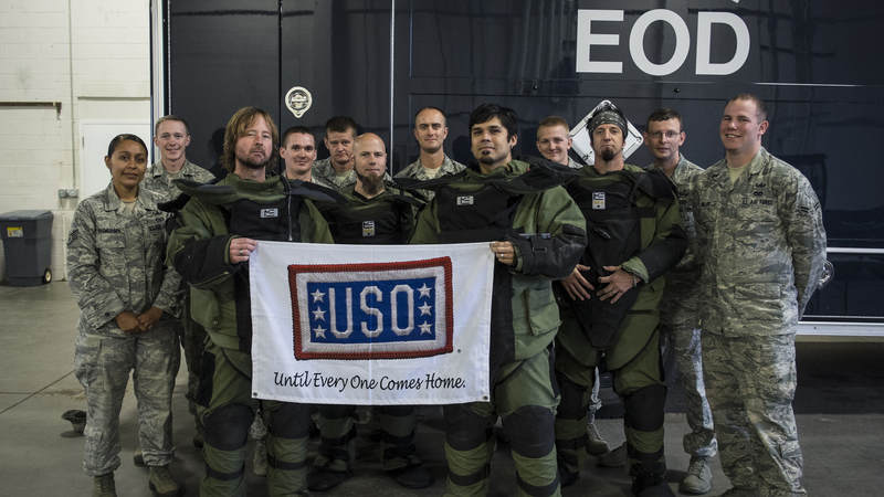 From left to right, Drowning Pool band members Stevie Benton, C.J. Pierce, Jasen Moreno and Mike Luce suit up with EOD troops during their USO tour to F.E. Warren AFB in Wyoming on Sept. 11, 2013.