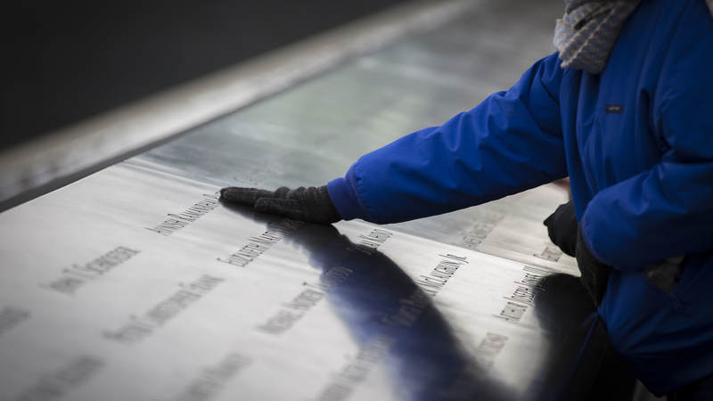 A visitor touches etchings at the National September 11 Memorial in New York.