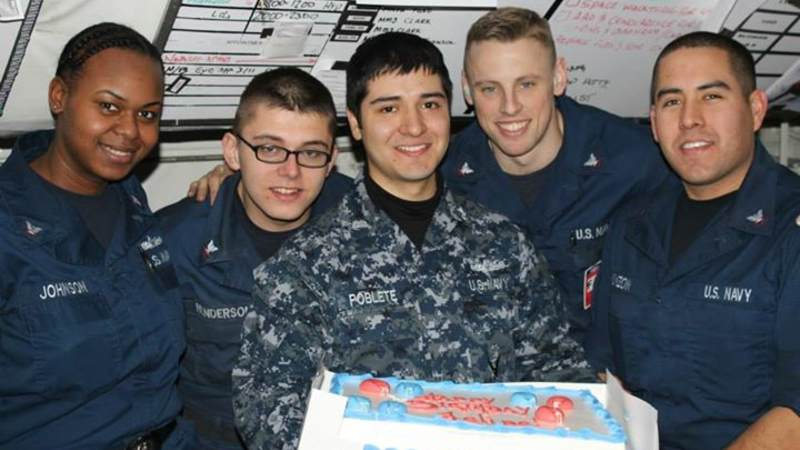 Sailors smile in front of an OBC surprise cake in Japan.