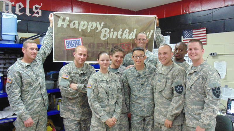 Soldiers smile in front of the birthday sign at Camp Humphreys, South Korea.