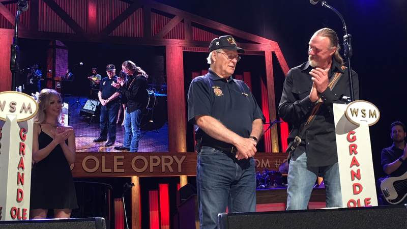 Trace Adkins cheers for USO volunteer Roland Forand as he's honored during Tuesday's celebration at the Grand Ole Opry.
