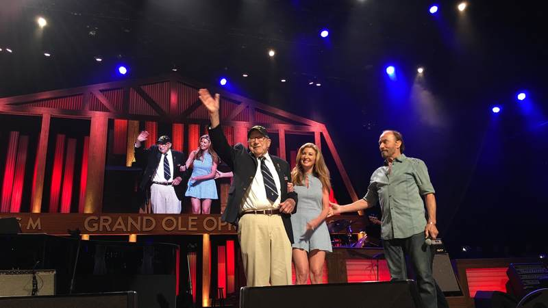 "Lee Greenwood honors Claude ""Dutch"" Mann, a World War II veteran, on Tuesday during the Grand Ole Opry's celebration of the USO's 75th anniversary."