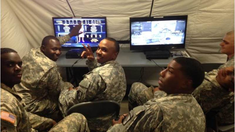 Soldiers deployed to Camp Buchanan, Liberia, play on gaming systems donated by USO at the Morale, Welfare and Recreation tent.