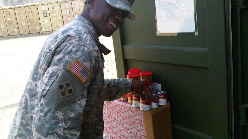 Army Sgt. 1st Class Maurice Blackburn pick up snacks donated by USO at the centralized distribution container.