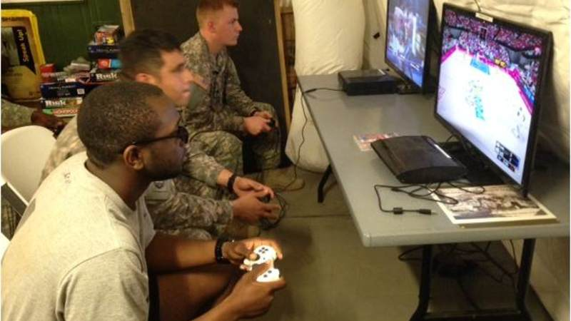 Soldiers play on gaming systems donated by USO at the Morale, Welfare and Recreation tent.