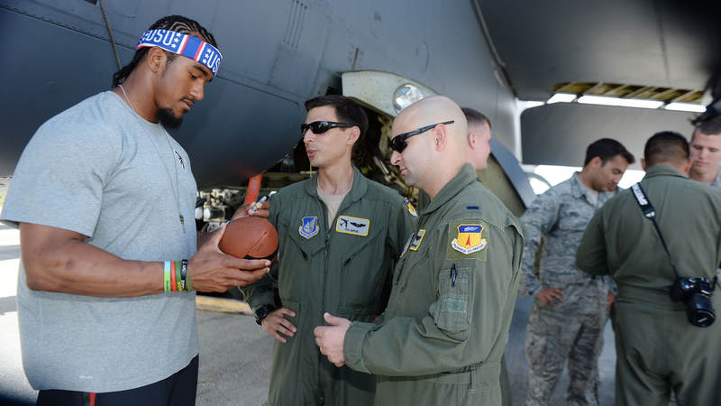 Atlanta Falcons linebacker Vic Beasley, left, signs autographs for service members during a weeklong USO/NFL tour to Guam and Hawaii.