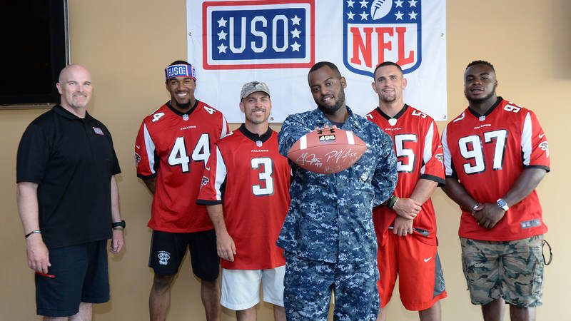 A sailor shows off a football signed by Atlanta Falcons coach Dan Quinn, left, and players Vic Beasley, Matt Bryant, Paul Worrilow and Grady Jarrett during a weeklong USO/NFL tour to Guam and Hawaii.