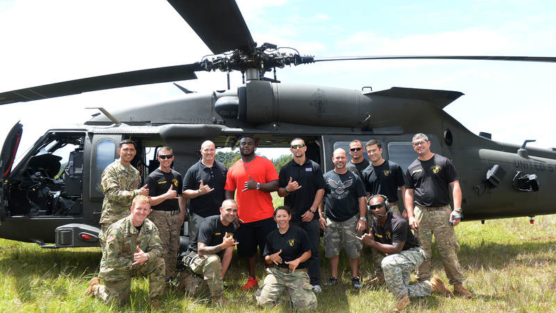 Atlanta Falcons players and head coach Dan Quinn check out an Army helicopter in Hawaii during a USO/NFL tour in June.