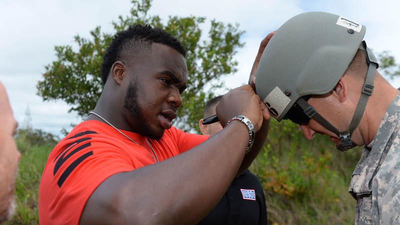 Atlanta Falcons defensive tackle Grady Jarrett signs a soldier's helmet during a weeklong USO/NFL tour to Guam and Hawaii.