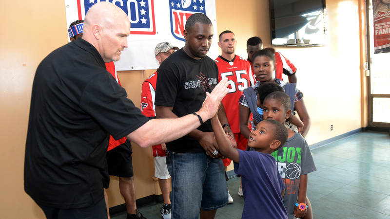 Atlanta Falcons head coach high-fives one of his littlest fans during a weeklong USO/NFL tour to Guam and Hawaii.