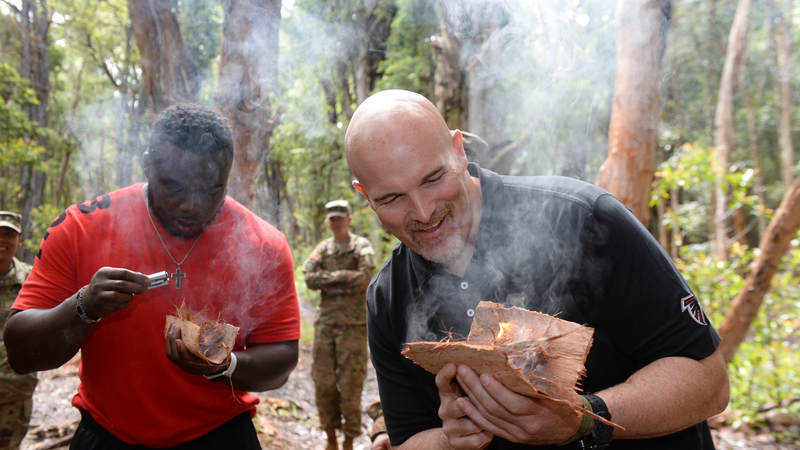 Soldiers (not pictured) teach Atlanta Falcons defensive tackle Grady Jarrett, left, and head coach Dan Quinn learn how to start a fire in a survival situation.