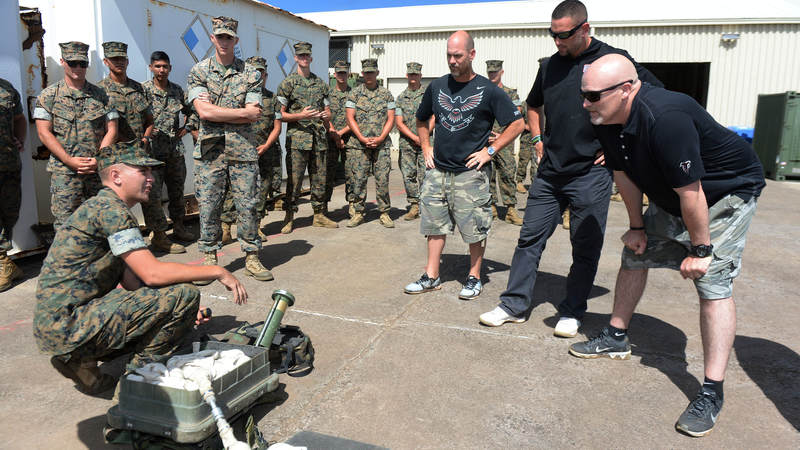 Atlanta Falcons kicker Matt Bryant, left, lineback Paul Worrilow, center, and head coach Dan Quinn learn the inner workings of a portable line charge, which is used to clear anti-personnel mines and wire obstacles.