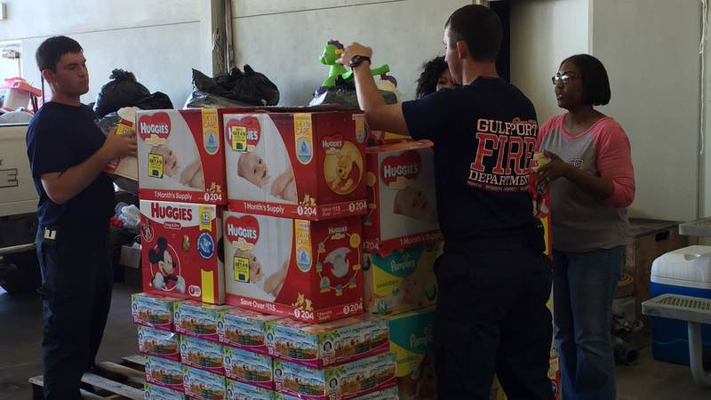 USO staffers Felice Kelly Gillum and Nicole Lewis assist Gulfport Fire Department sort relief supplies from the USO Gulf Coast supply drive for flood victims in Louisiana.