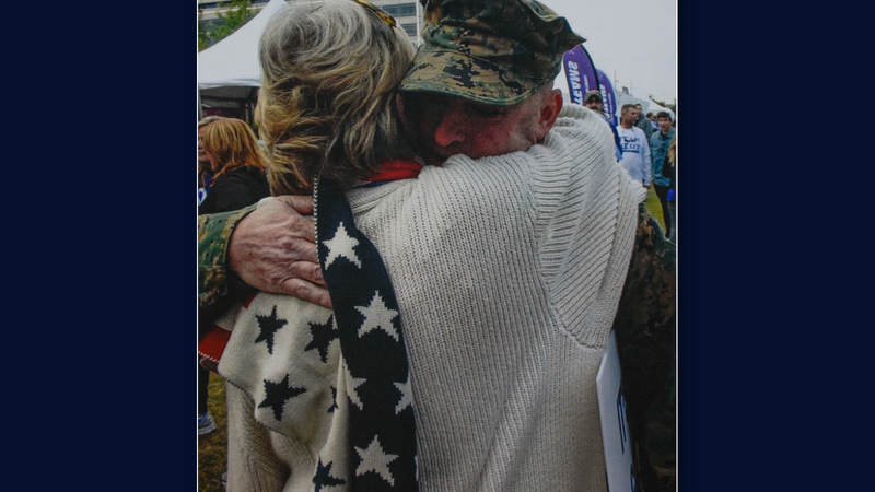 Suzanne Mitchell hugs a service member.