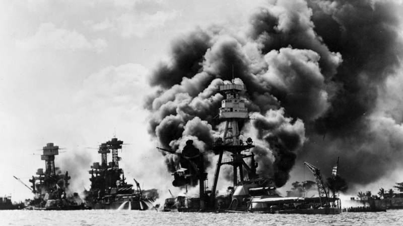 The USS Arizona burns and sinks following the Japanese sneak attack on Pearl Harbor, Hawaii, Dec. 7, 1941. In the background are the battleships USS West Virginia, left, and USS Tennessee, both damaged during the attack.