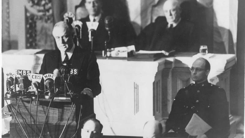 "President Franklin Delano Roosevelt delivers his ""Day of Infamy"" speech to Congress on December 8, 1941. Behind him are Vice President Henry Wallace, left, and Speaker of the House Sam Rayburn. To the right, in uniform in front of Rayburn, is Roosevelt's son James, who escorted his father to the Capitol."