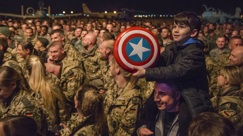 "A ""Captain America"" fan waits for actor Chris Evans to come on stage at a USO Chairman's Holiday Tour show at Al Udeid Airbase in Qatar."