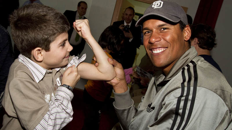 NFL veteran Donnie Edwards makes a new friend while visiting an orphanage in Izmir, Turkey, March 25, 2010. Edwards is joined by New Orleans Saints players Drew Brees and Billy Miller.
