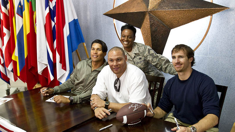 Donnie Edwards, Billy Miller and Drew Brees pose for a photo with U.S. Air Force Senior Master Sgt. Abigail Davis, from Tallahasse, FL at the NATO Allied Air Command in Izmir, Turkey, March 25, 2010.
