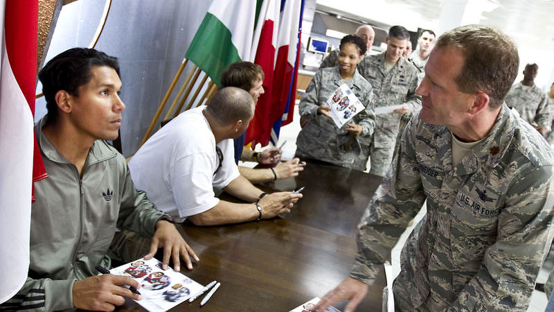 Donnie Edwards, Billy Miller and Drew Brees sign autographs for U. S. military personell and their families at the NATO Allied Air Command in Izmir, Turkey, March 25, 2010. Donnie Edwards is shown here with U. S. Air Force Major Stanton P. Schnieder, from Colorado Springs, CO.