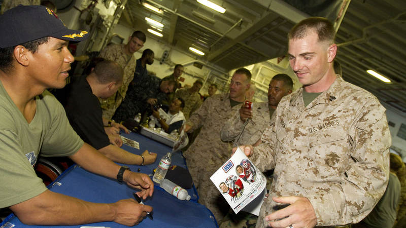 NFL and USO tour veteran Donnie Edwards signs an autograph for Marines and Sailors of the USS Nassau, March 28, 2010. Edwards is joined by fellow NFL players Drew Brees and Billy Miller, this marks the third USO tour for the trio, who will visit troops in Africa, Turkey and the Persian Gulf.