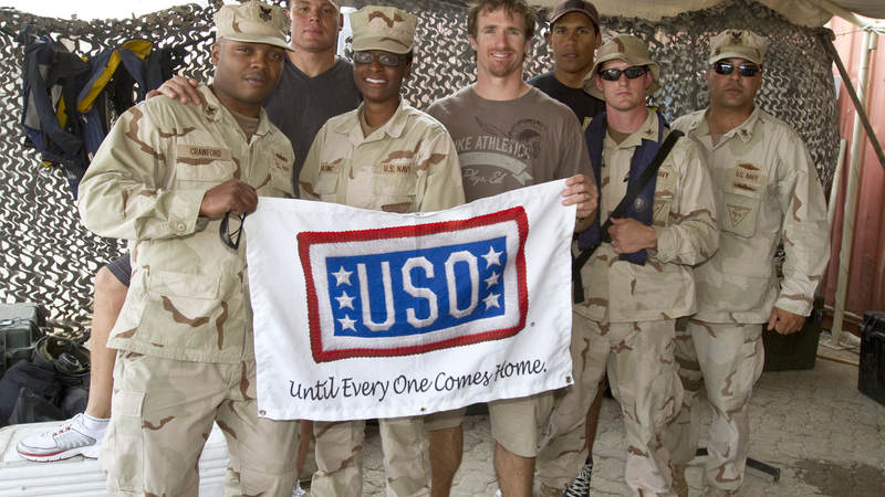 (L to R) NFL's Billy Miller, Drew Brees and Donnie Edwards pose for photos with members of Maritime Expeditionary Security Squadron Four stationed in Dubaii on March 27, 2010. This is the trio's third USO tour.