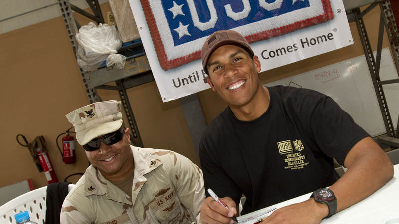 Former Kansas City Chiefs linebacker Donnie Edwards signs an autograph for U.S. Navy Gunners Mate Second Class Marvin Leon Ford, Jr. while in Dubaii on March 27, 2010.