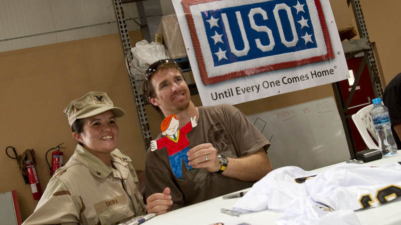 "Most Valueable Player"" Drew Brees poses for a photo with PS2 Lisa Dadurn of Pensacola, FL during a USO visit to Dubaii on March 27, 2010. While taking the picture, Brees holds up ""Flat Stanley"", a project of Dadura's second grade niece in Ft. Worth, TX."