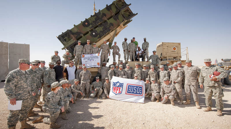 NFL players (L) Mario Williams-Houston Texans, Joe Thomas-Cleveland Browns (L-next to Williams), Jason Witten-Dallas Cowboys (center) and Vernon Davis-San Francisco 49ers (kneeling next to Witten) pose with the entire crew supporting the defensive missile system, March 3, 2010. On an eight-day, nine-base USO tour the four players are on a mission to visit with troops, sign autographs and boost morale.