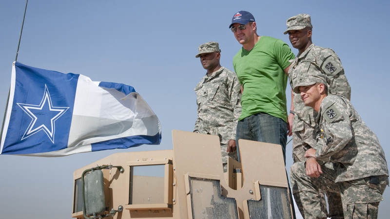 NFL player Jason Witten-Dallas Cowboys poses for a photo with Cowboys fans ontop of a Humvee proudly displaying a Cowboys flag, which Witten later autographed, March 3, 2010.  Traveling on his first USO tour Witten is joined by fellow NFL All Stars Vernon Davis-San Francisco 49ers, Joe Thomas-Cleveland Browns and Mario Williams-Houston Texans.