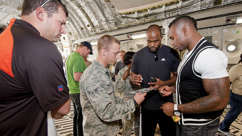 NFL players (L-R) Joe Thomas-Cleveland Browns, Jason Witten-Dallas Cowboys (background-green), Mario Williams-Houston Texans (R-Center), and Vernon Davis-San Francisco 49ers (R) sign autographs for the crew of a C-17 cargo aircraft at the airbase, March 3, 2010.