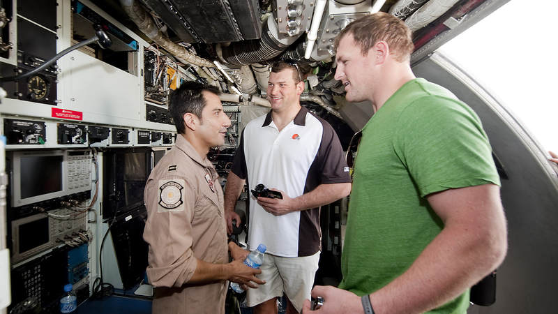 NFL players Joe Thomas-Cleveland Brown (C) and Jason Witten-Dallas Cowboys (R) get a tour of an RC 135/JSTARS aircraft from a service member, March 3, 2010. The two Pro Bowl players are joined by fellow Pro Bowlers Vernon Davis-San Francisco 49ers and Mario Williams-Houston Texans on their first USO tour, traveling to nine bases in eight days the players will sign autographs, participate in meet and greets and extend their gratitude to troops.