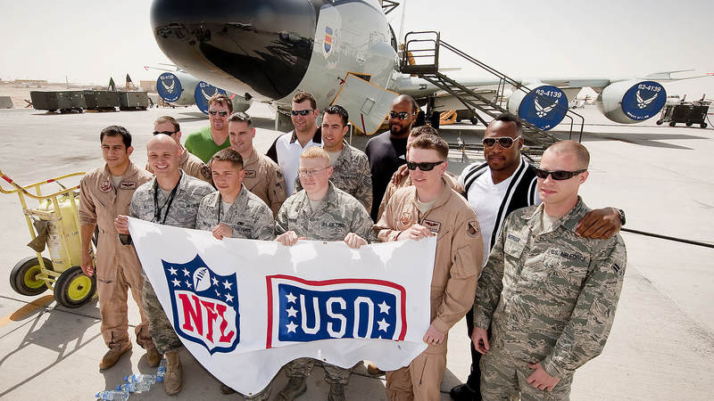 NFL players Jason Witten-Dallas Cowbys (L), Joe Thomas-Cleveland Browns (L-middle), Mario Williams-Houston Texans (R-middle) and Vernon Davis-San Francisco 49ers (R) pose for a group shot with the ground and air crew of a RC 135/JSTARS aircraft behind them, March 3, 2010.  The four NFL All Stars are taking part in their first USO tour, traveling to nine bases in eight days to boost morale, sign autographs and extend their thanks to America's troops.