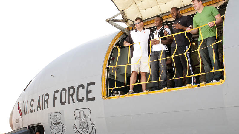 NFL players Vernon Davis-San Francisco 49ers (L-middle), Joe Thomas-Cleveland Browns(Left), Mario Williams-Houston Texans (R-middle) and Jason Witten-Dallas Cowboys (R) peer out the cargo door of a KC135-Aerial Tanker as they touchdown in the Persian Gulf, March 3, 2010.  The NFL 2010 All Star players are traveling on their first USO tour, the players will trek to nine bases in eight days to boost morale and bring a touch of home to troops.