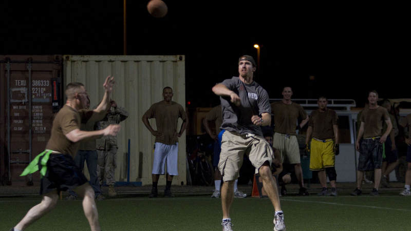 New Orleans Saints quarterback Drew Brees gets rushed by service members as he plays an exhibition football game with troops at Camp Lemonnier in Djibouti on March 29, 2010. Brees is in the region as part of a nine-day USO tour designed to boost morale and bring troops a touch of home.