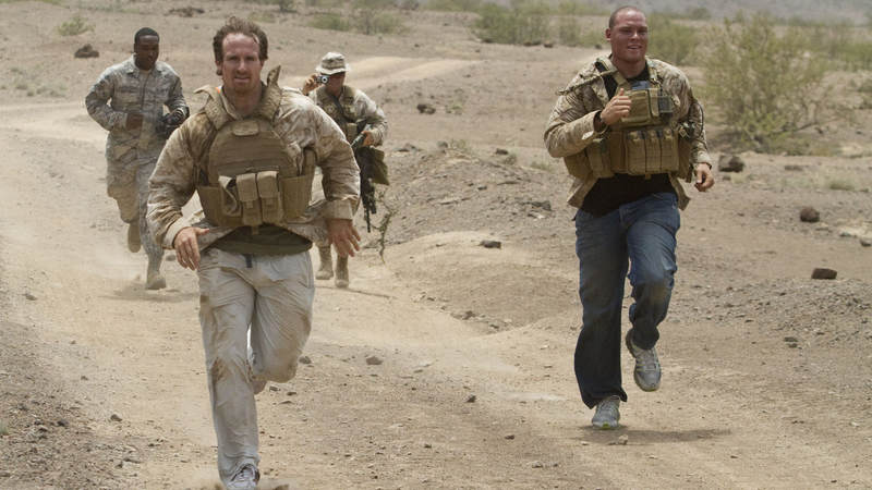 New Orleans Saints quarterback Drew Brees (Left) and tight end Billy Miller run to complete a U.S. Marine Corps grenade training exercise at Camp Lemonnier in Djibouti on March 29, 2010.  Joined by fellow NFL-er Donnie Edwards, the trio is in the region as part of a nine-day USO tour designed to boost morale and bring troops a touch of home.
