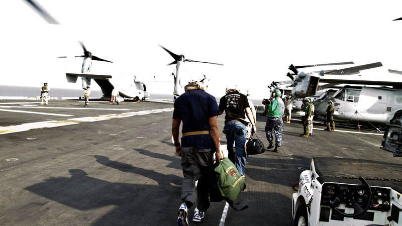 New Orleans Saints quarterback Drew Brees, former Kansas City Chiefs linebacker Donnie Edwards and New Orleans Saints tight end Billy Miller board a V-22 Osprey in route to the USS Nassau on March 29, 2010.  Traveling on their third USO tour together, the NFL trio also visited troops in Turkey and Dubaii as part of their nine-day USO tour.