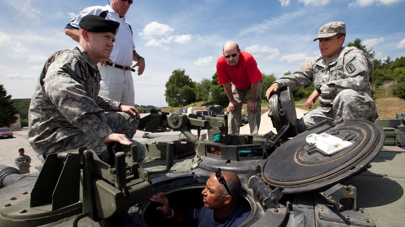 Two soldiers brief Carolina Panthers head coach John Fox (standing 2nd l), Minnesota Vikings head coach Brad Childress (standing 2nd r) and Cincinnati Bengals head coach Marvin Lewis (bottom in tank hatch) about the M1 Abrahms tank during a USO tour stop at Baumholder Army Garrison in Germany July 1, 2010.