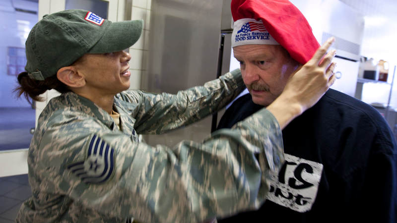Minnesota Vikings head coach Brad Childress gets some help after trading hats with TSgt Tamala Williams, a cook at a dining facility at Ramstein Air Base in Germany, during a USO tour stop on June 30, 2010.