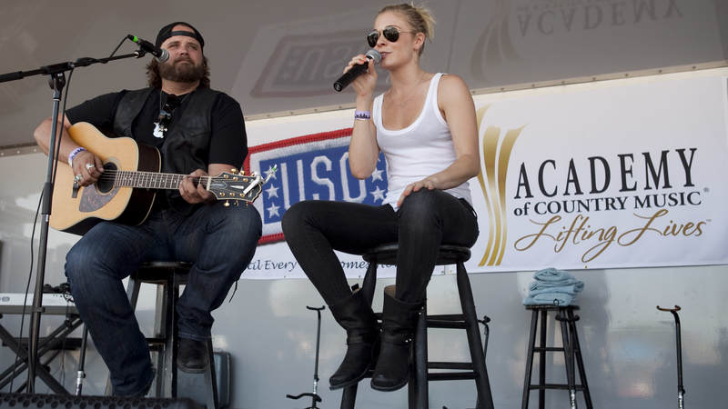Country music artists Randy Houser and LeAnn Rimes perform together during the USO/ACM Lifting Lives concert at Nellis Air Force Base in Las Vegas on April 17, 2010.