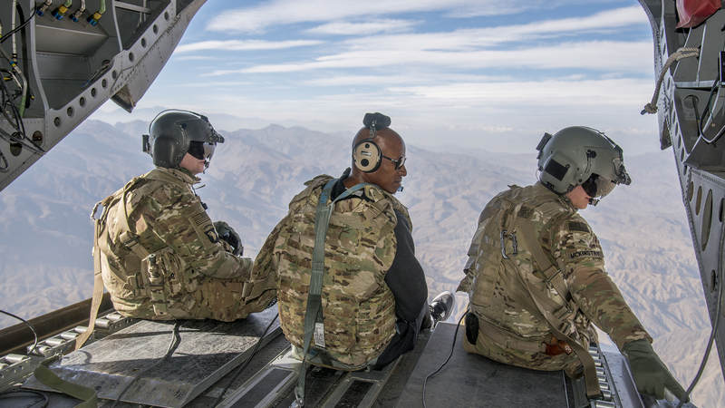 Former NBA star Ray Allen, center, sits on the back of an Army helicopter and looks out over Afghanistan during the USO Chairman's Holiday Tour in December 2016.