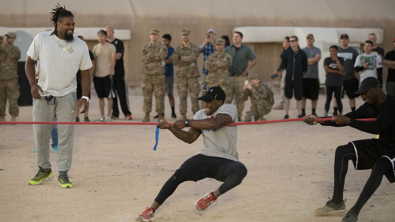 New Orleans Saints defensive end Cameron Jordan, left, cheers on service members competing in a USO-sponsored gridiron challenge during a USO/NFL tour stop in Southwest Asia on April 3.