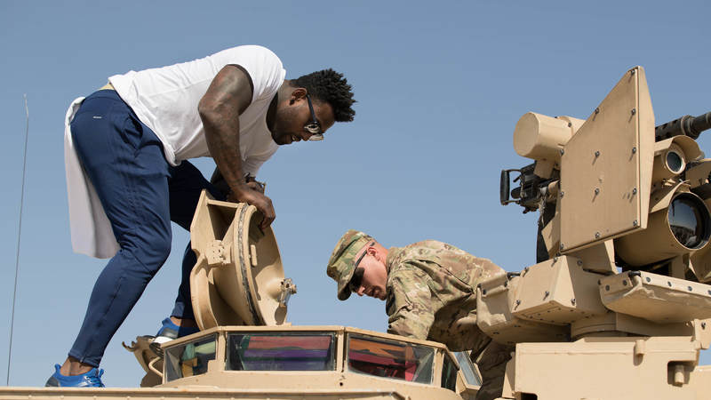 Tennessee Titans tight end Delanie Walker, left, talks with a service member while looking in the hatch of an armored vehicle during a USO/NFL tour stop in Southwest Asia on April 3.
