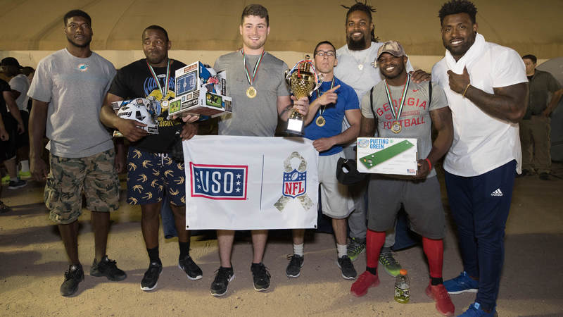 Miami Dolphins cornerback Byron Maxwell, left, New Orleans Saints defensive end Cameron Jordan, third from right, and Tennessee Titans tight end Delanie Walker, right, pose with the team that won a USO-sponsored gridiron challenge during an April 3 stop in Southwest Asia. The trio of NFL stars is on a weeklong USO/NFL tour to the region.