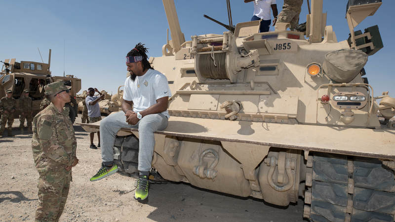 New Orleans Saints defensive end Cameron Jordan, second from left, and Tennessee Titans tight end Delanie Walker talk with service members on an armored vehicle during a USO/NFL tour stop in Southwest Asia on April 3.