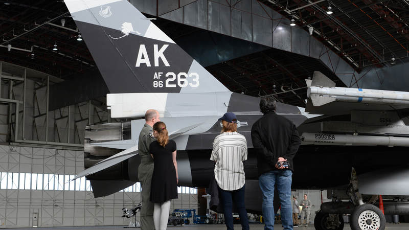 Air Force Col. Todd Robbins, the 354th Fighter Wing vice commander, speaks with Cassadee Pope and her tour manager about the F-16 Fighting Falcon aircraft April 8 at Eielson Air Force Base, Alaska.