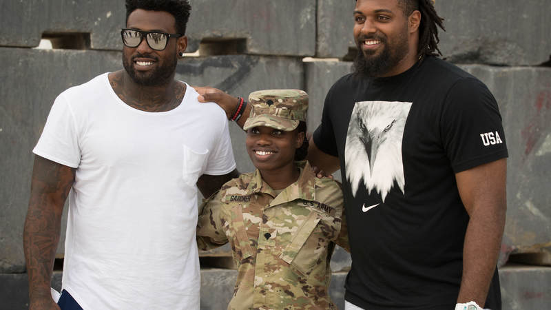 Tennessee Titans tight end Delanie Walker, left, and New Orleans Saints defensive end Cameron Jordan pose for a photo with a service member during a USO tour visit in the U.S. Fifth Fleet Area of Operations April 8.
