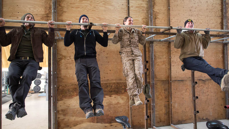 From left, Adam Rodriguez, Nick Zano and Channing Tatum (far right) have a pull-up contest with a service member during a USO tour stop in Afghanistan